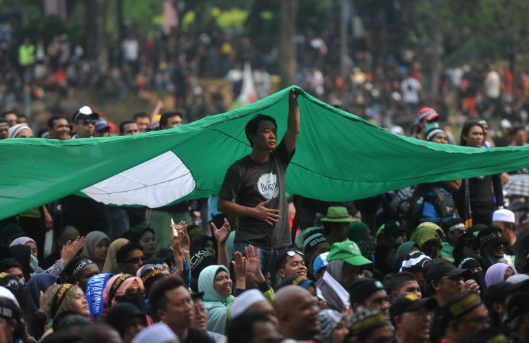 KUALA LUMPUR, MALAYSIA - Protester hold PAS flag as they gather under a large PAS flag during Blackout 505 #KL622 in Kuala Lumpur on Jun 22, 2013. The gathering's three main demands are for the Election Commission (EC) members to step down and a bipartisan interim panel be elected, for re-elections to be held in 30 parliamentary seats which Pakatan lost marginally and claims it has strong proof of misconduct and for the postponement of any delineation or amendments to the election law until a new EC is selected.PHOTO/FIRDAUS LATIF