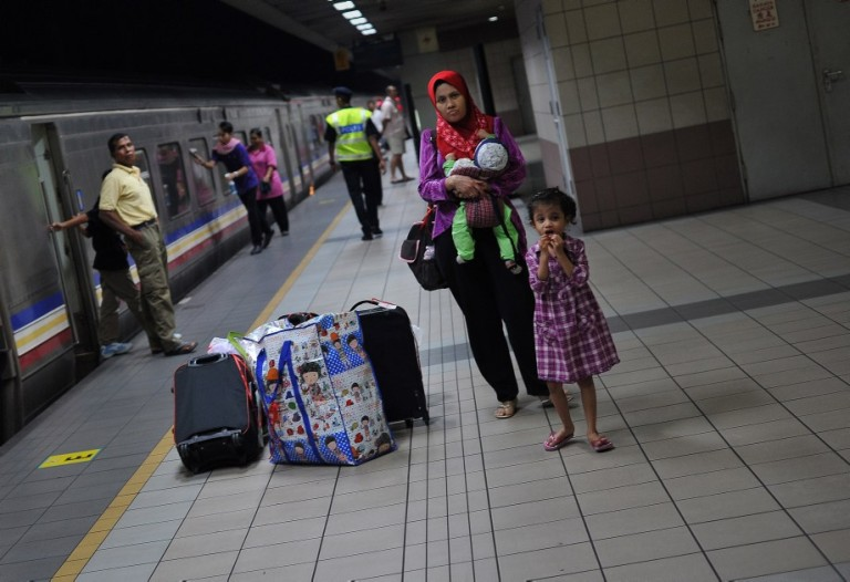 KUALA LUMPUR, MALAYSIA -  Passengers wait for a train which will take them to their home villages for the August 8 Eid al Fitr holiday in Kuala Lumpur on August 6, 2013. In the days ahead of the Eid al Fitr holiday, millions of Malaysian working in Kuala Lumpur return to their hometowns to celebrate the holiday with family. Photo by Firdaus Latif