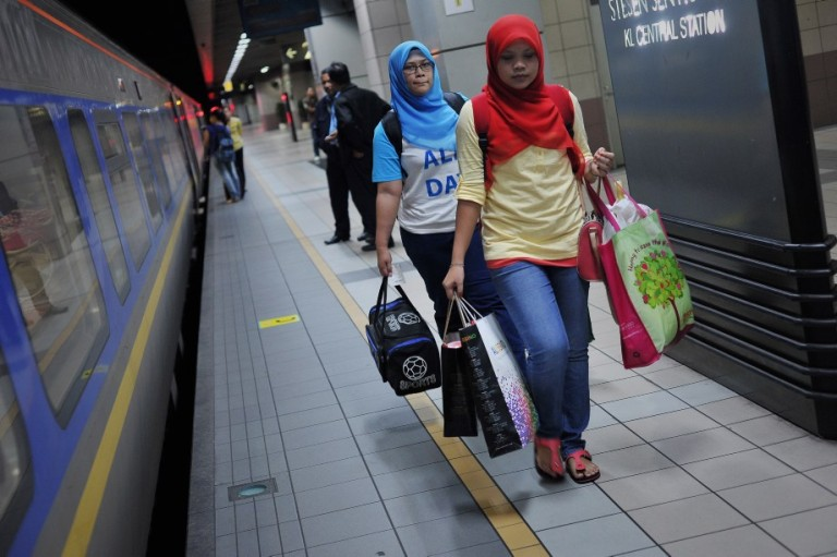 KUALA LUMPUR, MALAYSIA -  Passengers carry their baggage into a train which will take them to their home villages for the August 8 Eid al Fitr holiday in Kuala Lumpur on August 6, 2013. In the days ahead of the Eid al Fitr holiday, millions of Malaysian working in Kuala Lumpur return to their hometowns to celebrate the holiday with family.Photo by Firdaus Latif