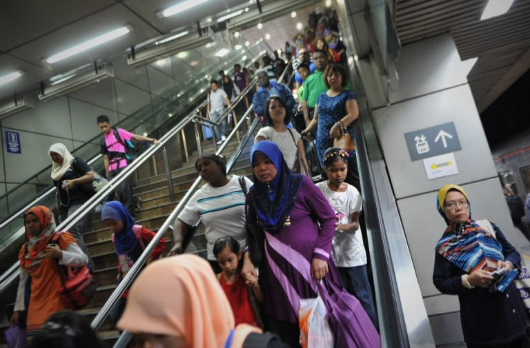 KUALA LUMPUR, MALAYSIA - Passengers use escalator to the tracks to catch a train which will take them to their home villages for the August 8 Eid al Fitr holiday in Kuala Lumpur on August 6, 2013. In the days ahead of the Eid al Fitr holiday, millions of Malaysian working in Kuala Lumpur return to their hometowns to celebrate the holiday with family.Photo by Firdaus Latif