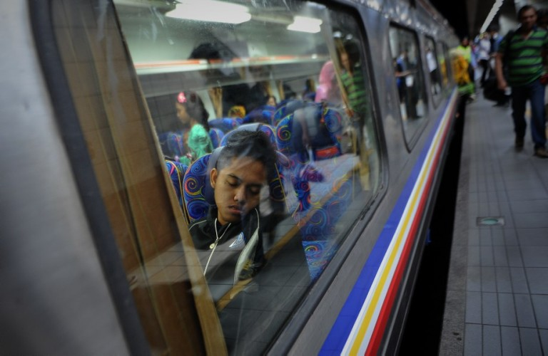 KUALA LUMPUR, MALAYSIA -  A Passengers take a nap in a train which will take them to their home villages for the August 8 Eid al Fitr holiday in Kuala Lumpur on August 6, 2013. In the days ahead of the Eid al Fitr holiday, millions of Malaysian working in Kuala Lumpur return to their hometowns to celebrate the holiday with family.Photo by Firdaus Latif
