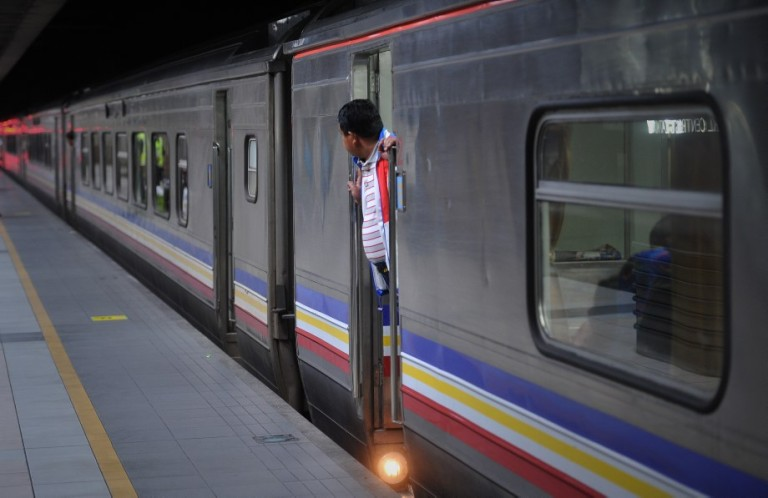 KUALA LUMPUR, MALAYSIA - Passengers looks out of a train which will take them to their home villages for the August 8 Eid al Fitr holiday in Kuala Lumpur on August 6, 2013. In the days ahead of the Eid al Fitr holiday, millions of Malaysian working in Kuala Lumpur return to their hometowns to celebrate the holiday with family.Photo by Firdaus Latif