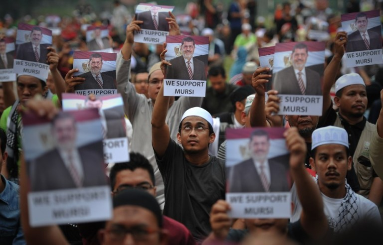 KUALA LUMPUR, MALAYSIA - Malaysian Islamist holds a poster of ousted Egyptian President Mohamed Morsi during a rally to oppose the military overthrow of the Islamist leader and subsequent killings, in Kuala Lumpur on August 17, 2013.Photo by Firdaus Latif