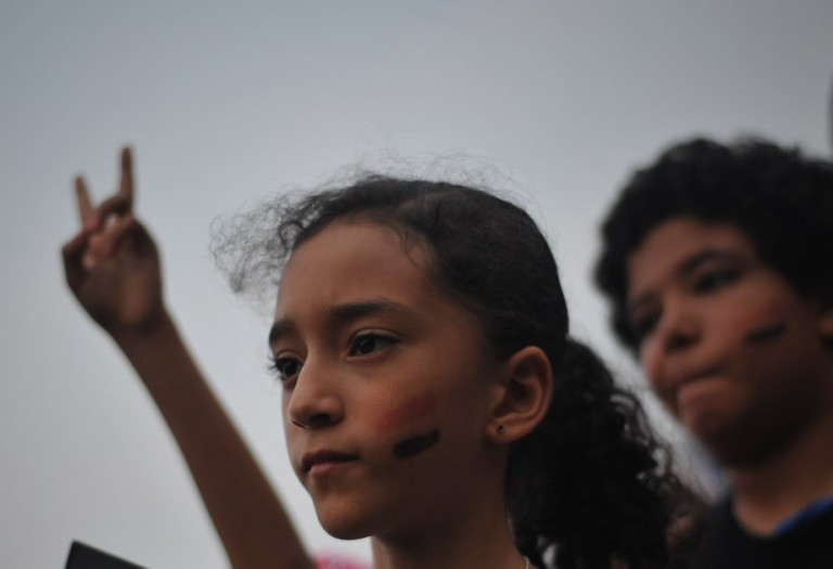 KUALA LUMPUR, MALAYSIA - An Egyptian child face painted with the colours of the Egyptian national flag during a rally to oppose the military overthrow of the Islamist leader and subsequent killings, in Kuala Lumpur on August 17, 2013. Photo by Firdaus Latif