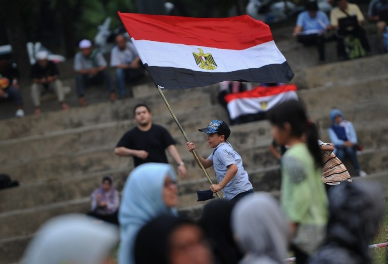 KUALA LUMPUR, MALAYSIA - An Egyptian youth living in Malaysia plays with his country's national flag during a rally to oppose the military overthrow of the Islamist leader and subsequent killings, in Kuala Lumpur on August 17, 2013.Photo by Firdaus Latif