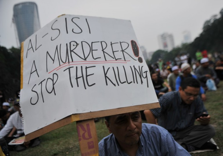 KUALA LUMPUR, MALAYSIA - Malaysian Islamist hold placards during a rally to oppose the military overthrow of the Islamist leader and subsequent killings, in Kuala Lumpur on August 17, 2013.Photo by Firdaus Latif