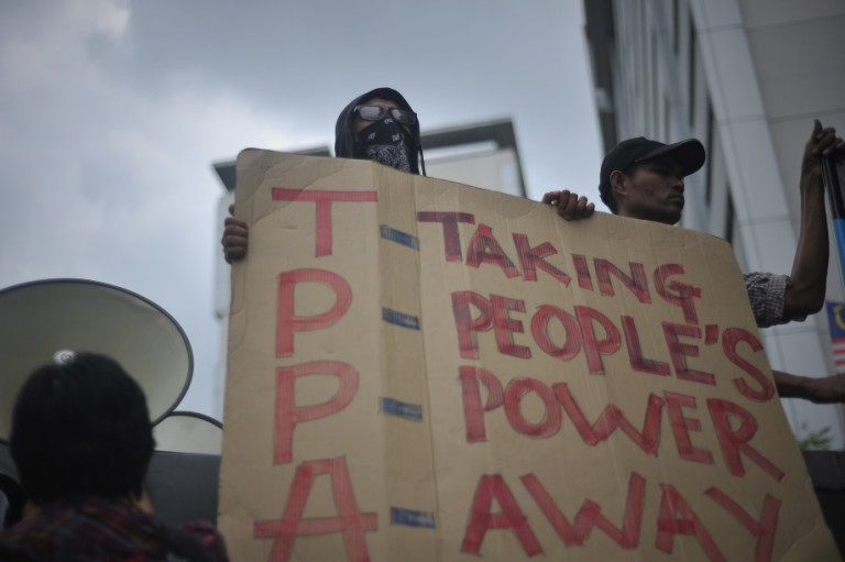Demonstrator hold placards during a protest against Malaysia's participation in rule-making negotiations for the Trans-Pacific Partnership agreement (TPP) in Kuala Lumpur on August 23, 2013. Agreement of TPPA (Trans Pacific Partership Agreement) is only profitable corporate community which is 1% of Malaysian population.99% of Malaysians will lose. Photo by Firdaus Latif