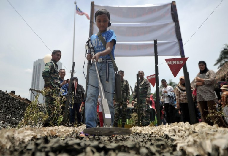 A boy tests his mine detection skills during the Armed Forces 80th Anniversary celebration in Kuala Lumpur, Malaysia, 21 September 2013. Photo by Firdaus Latif