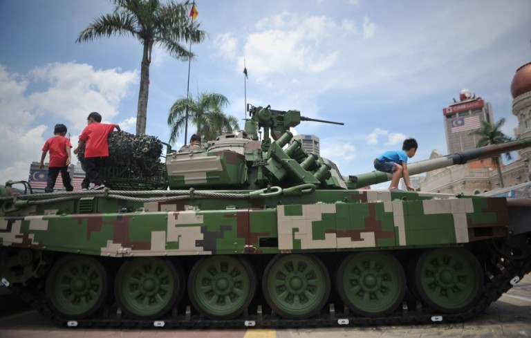 Children playing with Malaysian military tank on display during the Armed Forces 80th Anniversary celebration in Kuala Lumpur, Malaysia, 21 September 2013. Photo by Firdaus Latif