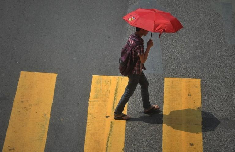 A man use umbrella walking at Pedestrian Crossing  in Kuala Lumpur, Malaysia, 23 September 2013. Photo by Firdaus Latif