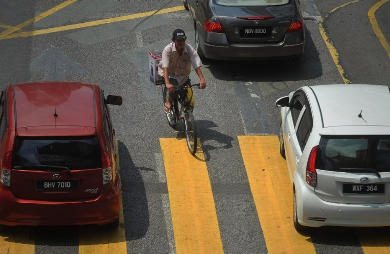 A man ride bicycle through the streets at Pedestrian Crossing in Kuala Lumpur, Malaysia, 23 September 2013. Photo by Firdaus Latif