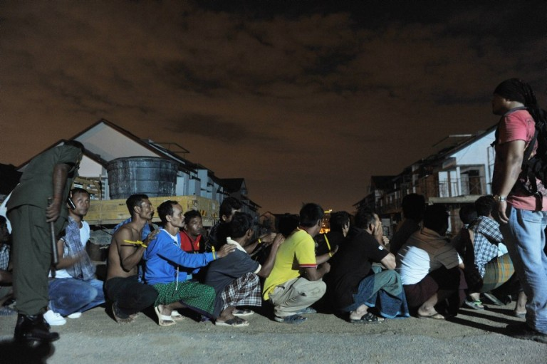 Illegal foreign workers handcuffed with zip-ties sitting on the ground lined up before walking to a truck during an immigration raid operation shortly after midnight in Klang, outside Kuala Lumpur on September 1 2013. Malay Mail/Firdaus Latif