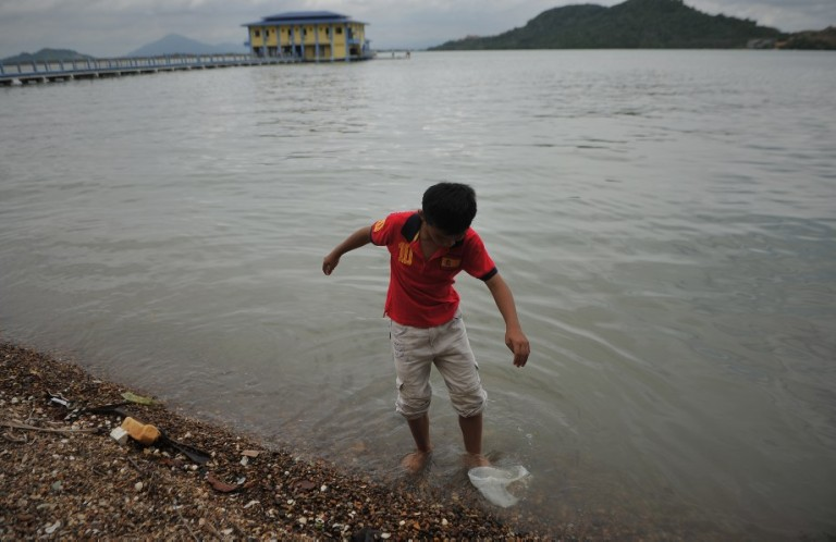 A boy try to remove plastic bag in a sea at Pulau Aman in Penang on October 5, 2013. Photo by Firdaus Latif