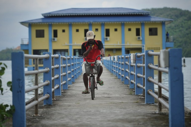 A man uses his mobile phone on a bicycle as he rides at Pulau Aman in Penang on October 5, 2013. Photo by Firdaus Latif