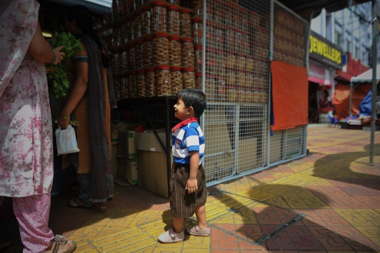 A young boy cry as his waiting for his mother browse cookies ahead of the upcoming Diwali festival celebrations at the Brickfields area, also known as Little India in Kuala Lumpur, Malaysia on October 29, 2013.  Photo: Firdaus Latif