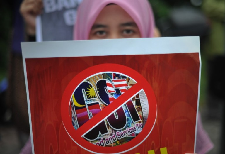 A women cover her faces with anti-Goods and Services Tax (GST) placards during a protest as they gather in front of Parliament House in Kuala Lumpur, Malaysia on October 25, 2013. Malaysia will finally implement the long-delayed Goods and Services Tax (GST) at 6 per cent beginning April 2015, during Prime Minister Datuk Seri Najib Razak announced the Budget 2014. Photo: Firdaus Latif