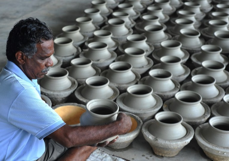 A Man potter cleaned newly-made earthen pots before dry in the sun at his workshop in Kuala Selangor outside Kuala Lumpur, Malaysia on October 26, 2013. Pottery is the ceramic material which makes up potterywares, of which major types include earthenware, stoneware and porcelain. Pottery also refers to the art or craft of a potter or the manufacture of pottery.  Photo: Firdaus Latif