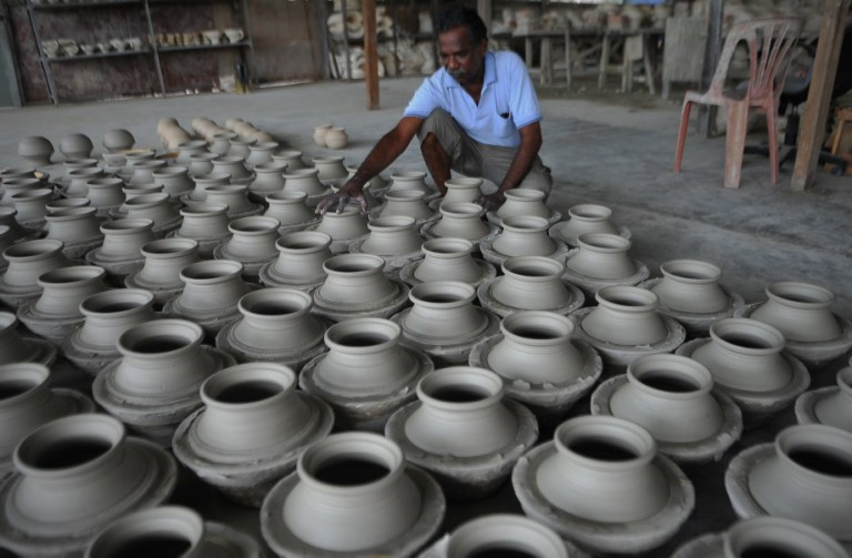A Man potter arranges newly-made earthen pots at his workshop in Kuala Selangor outside Kuala Lumpur, Malaysia on October 26, 2013. Pottery is the ceramic material which makes up potterywares, of which major types include earthenware, stoneware and porcelain. Pottery also refers to the art or craft of a potter or the manufacture of pottery.  Photo: Firdaus Latif