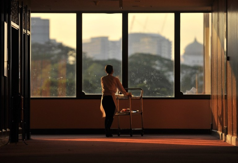 A woman in silhouette pushing food trolley to kitchen in Kuala Lumpu, Malaysia on October 7, 2013. Photo by Firdaus Latif