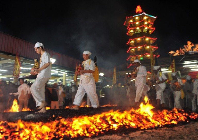 Malaysian Chinese devotees walk on a bed of hot coals during the Chinese Nine Emperor Gods Festival in Kuala Lumpur on October 13, 2013. The nine-day Taoist festival, believers welcome the Òemperor godsÓ who they believe live amongst the stars, in order to bring good fortune, longevity and good health. Some devotees stay at a temple during the festival, which begins on the eve of the ninth lunar month of the Chinese calendar, where they consume vegetarian meals and recite continuous prayers Photo: Firdaus Latif