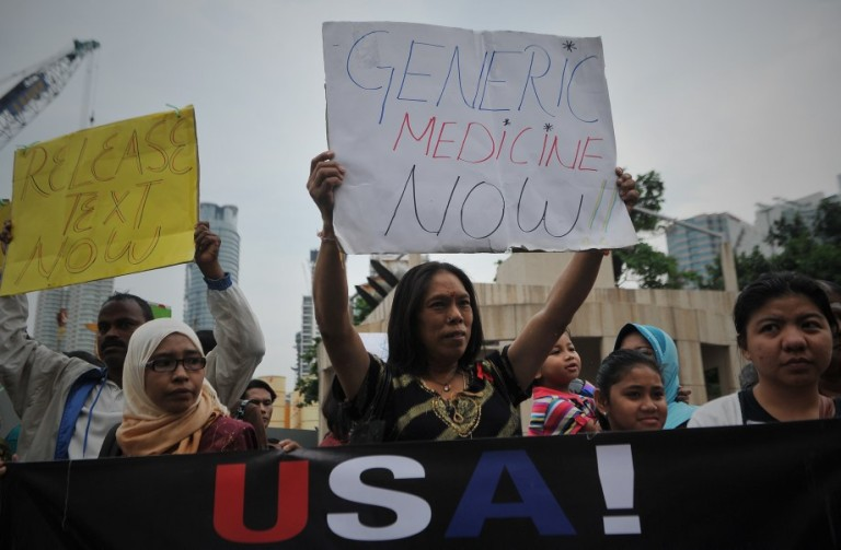 Protesters holds a placard condemning United States policy on free medication during a protest against the Trans-Pacific Partnership Agreement (TPPA) in Kuala Lumpur on October 11, 2013. Activists protested outside the Global Entrepreneurship Summit. Photo: Firdaus Latif