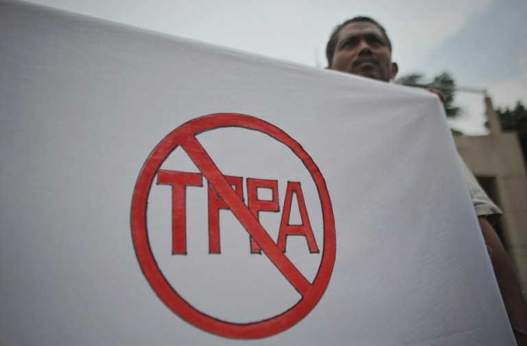 A protester holds a banner the anti Trans-Pacific Partnership Agreement (TPPA) logo during a protest against the Trans-Pacific Partnership Agreement (TPPA) in Kuala Lumpur on October 11, 2013. Activists protested outside the Global Entrepreneurship Summit. Photo: Firdaus Latif