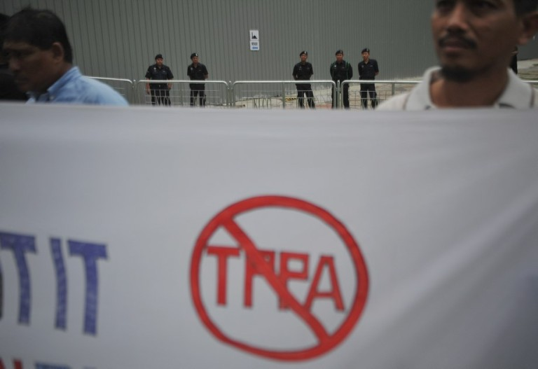 Police officers look on protester during a protest against the Trans-Pacific Partnership Agreement (TPPA) in Kuala Lumpur on October 11, 2013. Activists protested outside the Global Entrepreneurship Summit. Photo: Firdaus Latif