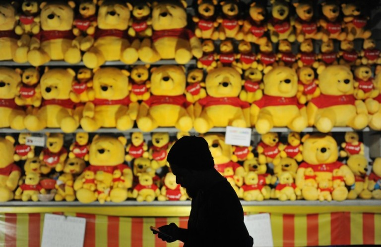 A man in silhouette walk past a Winnie the Pooh bears on display for visitors to try play a game and win a prize during Fun Fair at Penang outside Kuala Lumpur on November 29, 2013. Photo by Firdaus Latif