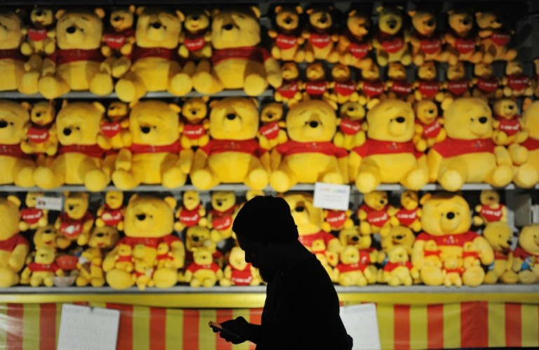 A man in silhouette walk past a teddy bear on display for visitors to try play a game and win some bears during Fun Fair at Penang outside Kuala Lumpur on November 29, 2013. Photo by Firdaus Latif