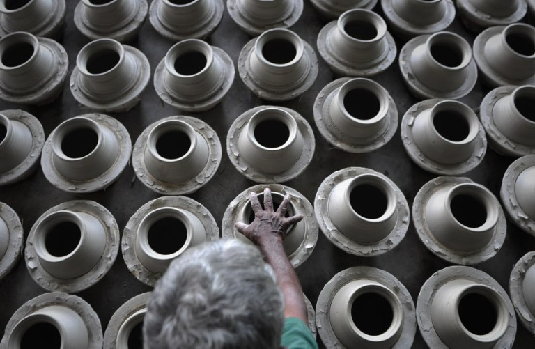 A worker potter arranges newly-made earthen pots at his workshop in Kuala Selangor outside Kuala Lumpur, Malaysia on October 26, 2013. Pottery is the ceramic material which makes up potterywares, of which major types include earthenware, stoneware and porcelain. Pottery also refers to the art or craft of a potter or the manufacture of pottery.. Photo by Firdaus Latif