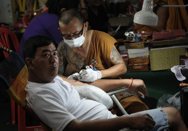 This photo taken on  October 13, 2013 Show A Thai Buddhist monk draws a tattoo on the shoulder of a man during the Chinese Nine Emperor Gods Festival in Kuala Lumpur.Photo: Firdaus Latif