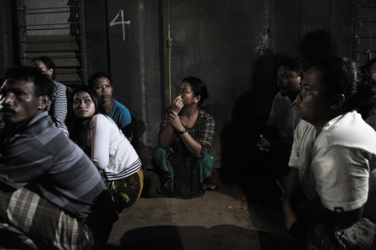 KUALA LUMPUR, MALAYSIA - illegal foreign workers waits before his documents to be checked during an immigration raid operation shortly after midnight in Klang, outside Kuala Lumpur on September 1 2013.Photo by Firdaus Latif