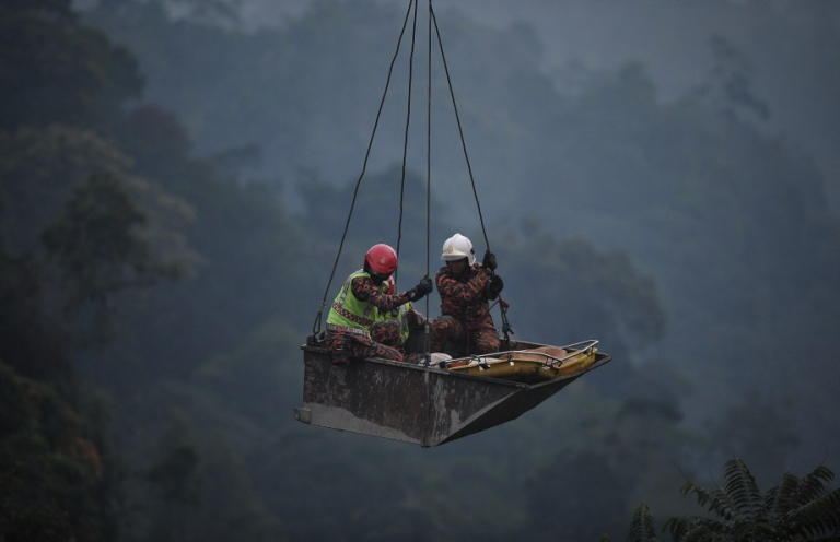 MALAYSIA, GENTING HIGHLANDS : Rescue workers use a crane to lift dead passengers after a bus crash when an express bus plunged down a 200-foot deep ravine near Genting Highlands on August 21, 2013.At least 37 people are confirmed dead after a bus tumbled into a deep ravine Wednesday in the country's worst-ever road accident, an official said.Photo by Firdaus Latif