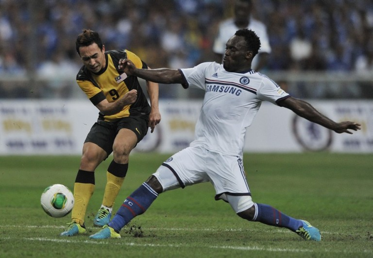 KUALA LUMPUR, MALAYSIA - JULY 21: Michael Essien of Chelsea tackles Norsharul of Malaysia during the match between Chelsea and Malaysia XI on July 21, 2013 at the Shah Alam Stadium in Shah Alam. Photo by Firdaus Latif