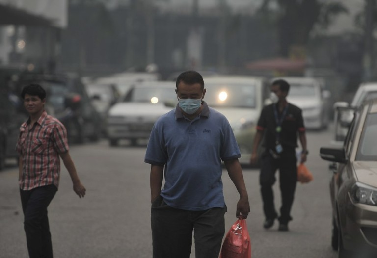 Kuala Lumpur,24/06/2013. People wearing face masks walk on the street in Section 14, Petaling Jaya.Photo by Firdaus Latif