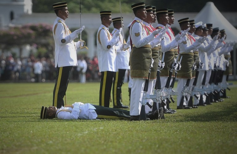 KUALA LUMPUR, MALAYSIA -  A royal guard fainting on the grass as his march in front of Malaysia's 14th King  Tuanku Abdul Halim Mu'adzam Shah during Malaysia's 14th King Tuanku Abdul Halim Mu'adzam Shah birthday celebration in Kuala Lumpur, Malaysia, 08 June 2013. Tuanku Abdul Halim Mu'adzam Shah is the 14th and current Yang di-Pertuan Agong of Malaysia, He previously served as the fifth Yang di-Pertuan Agong from 1970 to 1975. He is the first person to hold the position twice, as well as the oldest elected to the office. Photo by Firdaus Latif