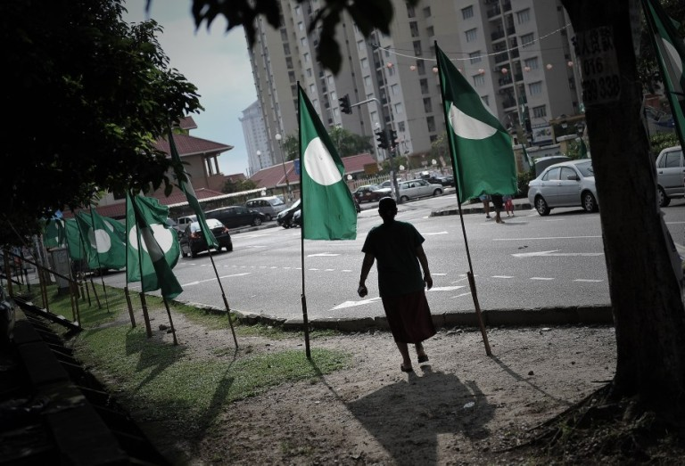 A Women in silhouette stand beside a flag of (PAS) Pan-Malaysian Islamic Party on display ahead of Malaysia general election on May 5 in Kuala Lumpur 27 April 2013.Photo by Firdaus Latif