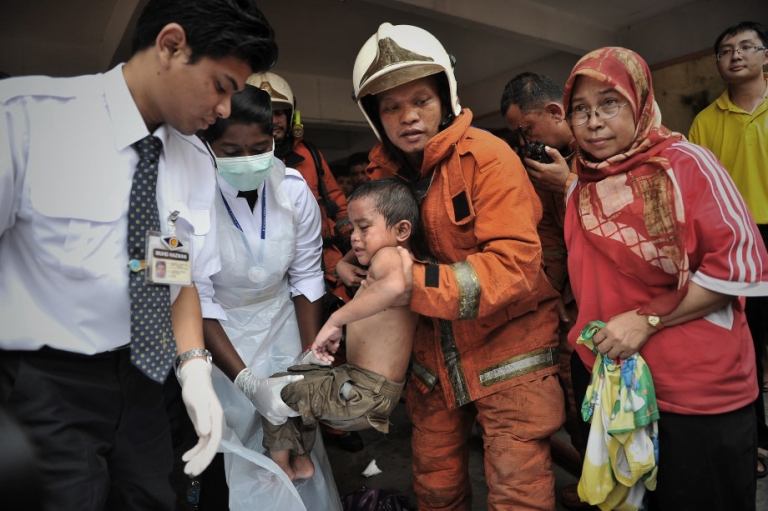 Kuala Lumpur,23/04/2013. A firefighters with nurse provide assistance to children who trapped fire in flats 700 at Taman kencana. Photo by Firdaus Latif