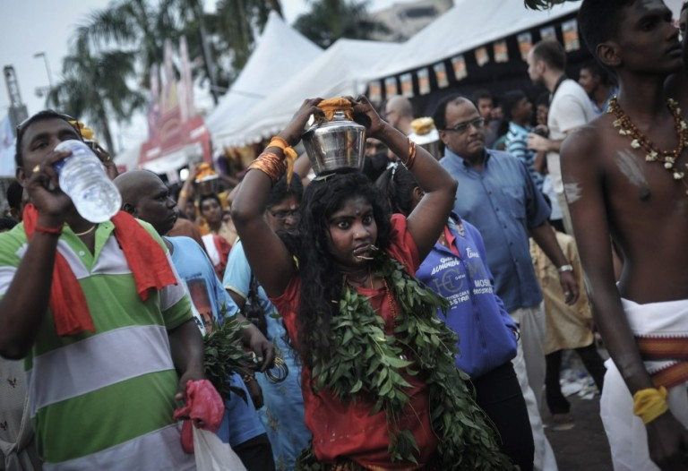 Hindu devotees carry milk pots on their heads for offering as they walk toward to the entrance of the Batu Caves during the Thaipusam procession in Batu Caves, Malaysia on January 17, 2014. Photo by Firdaus Latif