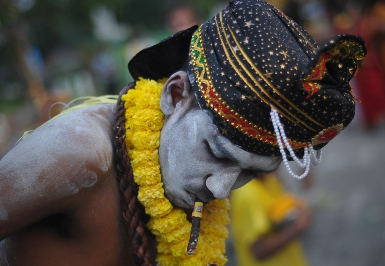 A Hindu devotee smokes a cigar while preparing for a procession during the Thaipusam procession in Batu Caves, Malaysia on January 17, 2014. Photo by Firdaus Latif