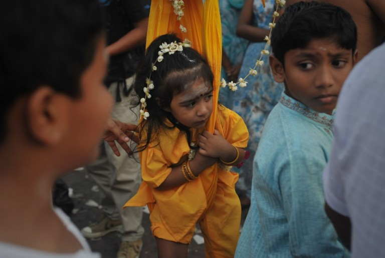 A young girl on sling during the Thaipusam procession in Batu Caves, Malaysia on January 17, 2014. Photo by Firdaus Latif
