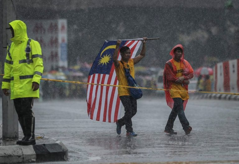 A protestor covers his head with the national flag during BERSIH 4.0 (The Coalition for Free and Fair Elections) in Kuala Lumpur on August 30, 2015. Photo by Firdaus Latif
