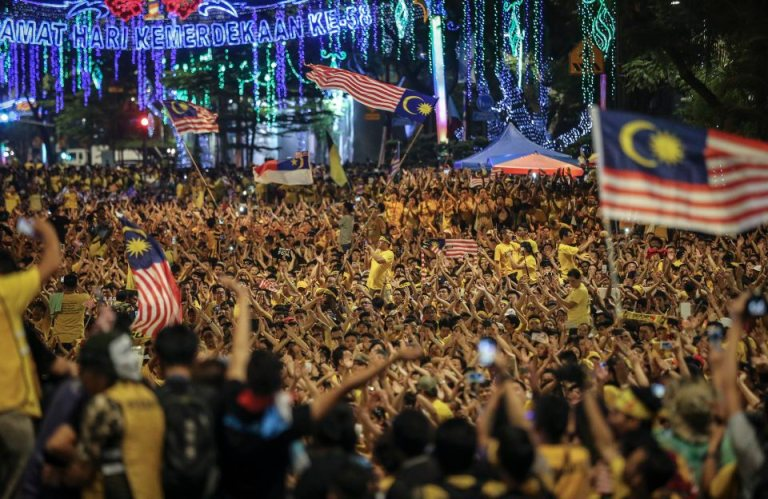 Malaysian protestors wave the national flag while amongst thousands of protestors seated along the streets during BERSIH 4.0 (The Coalition for Free and Fair Elections) in Kuala Lumpur on August 30, 2015. Photo by Firdaus Latif