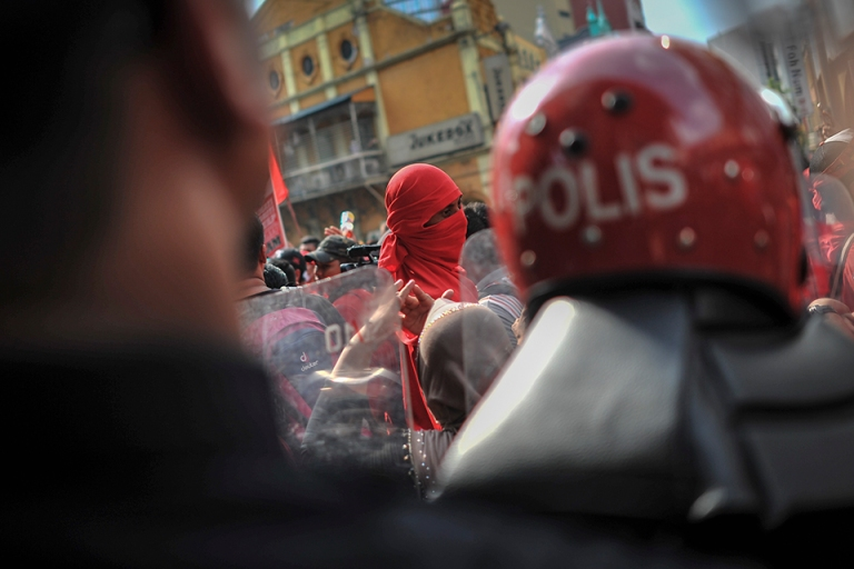 A protester covering his face with t-shirt during a pro-government Red Shirts rally in Kuala Lumpur on September 16, 2015. PHOTO BY FIRDAUS LATIF
