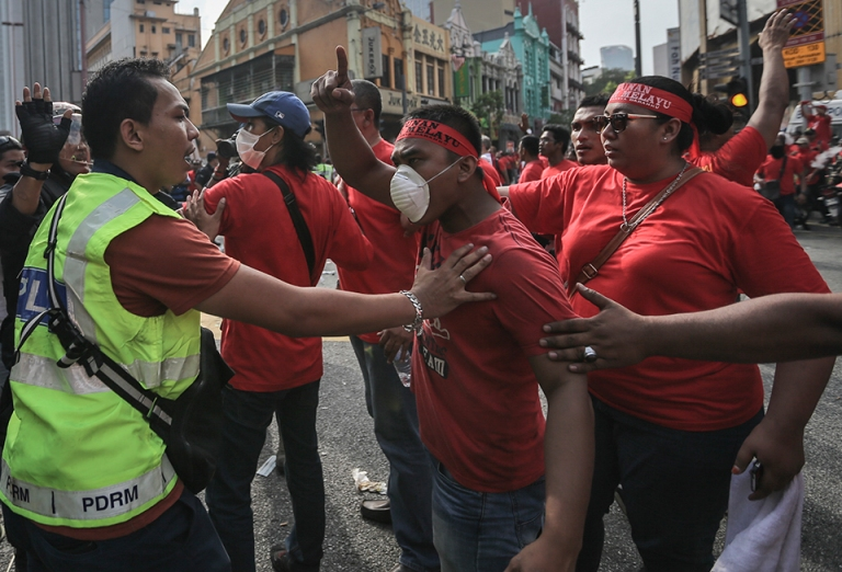 A protestor gestures towards police officers during a pro-government Red Shirts rally in Kuala Lumpur on September 16, 2015. PHOTO BY FIRDAUS LATIF