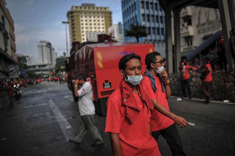 A protester walks past a water cannon truck during a pro-government Red Shirts rally in Kuala Lumpur on September 16, 2015. PHOTO BY FIRDAUS LATIF